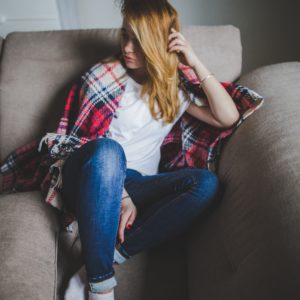 young woman looking depressed sitting on sofa