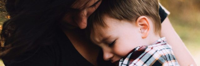 mother hugging young son both looking upset