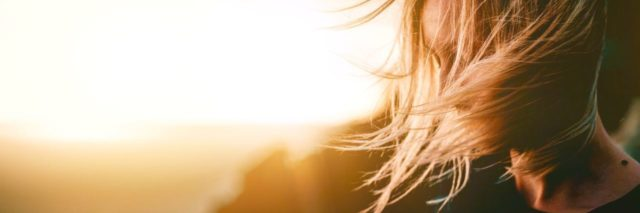 young woman with blonde hair at sunset looking peaceful