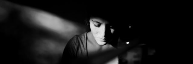 woman in black and white. face illuminated by light coming in from window