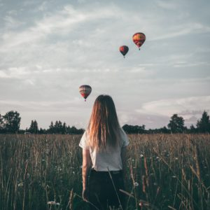 young woman standing in field watching hot air balloons in distance