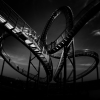 black and white photo of people walking on roller coaster like staircase, with the words sponsored by novartis in the corner