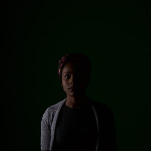 portrait of African American woman standing with black background