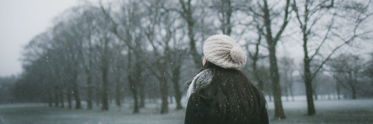 a woman stands outside in the winter