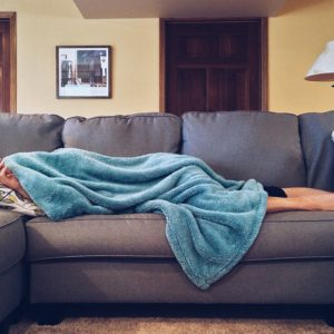 woman laying on couch under blanket