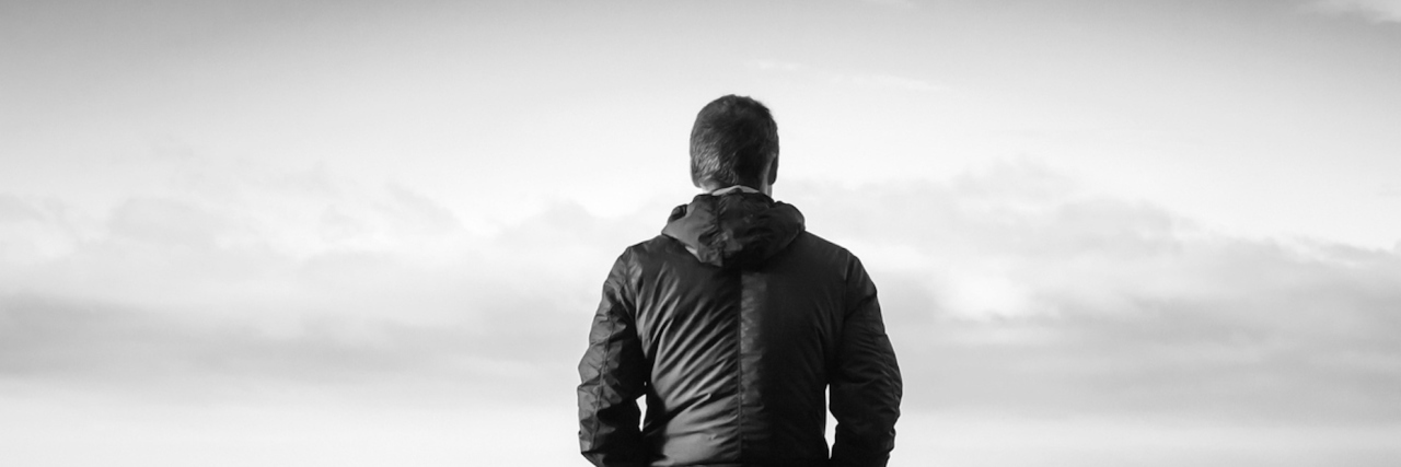 Young man in front of gray sky