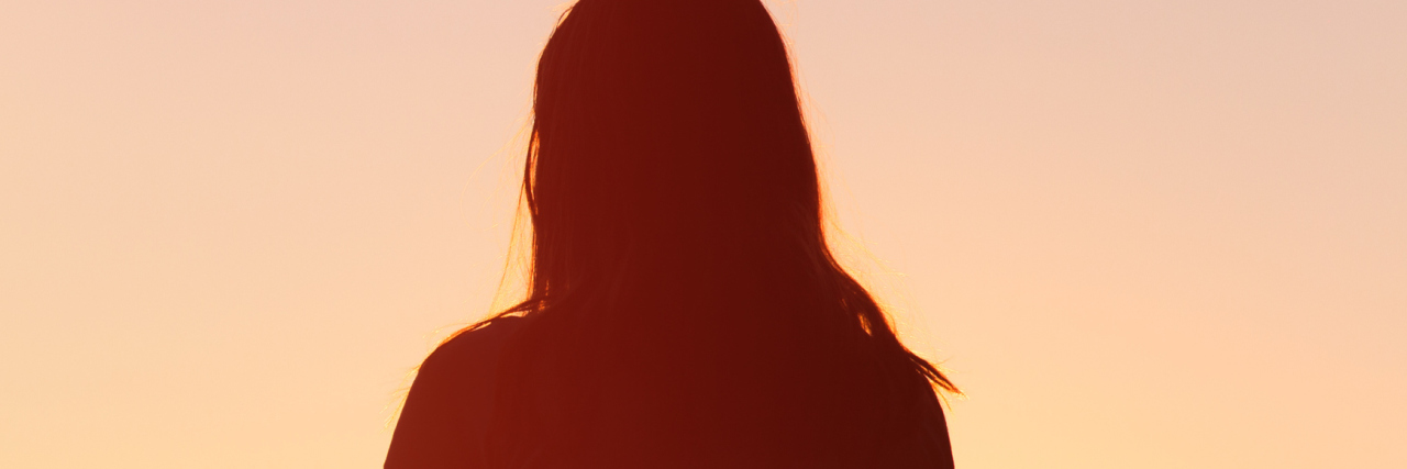 Silhouette of woman facing sunset sky