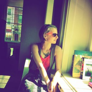 woman wearing sunglasses and looking out a window