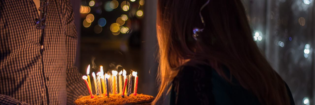 man holds birthday cake with lit candles as woman blows the candles out