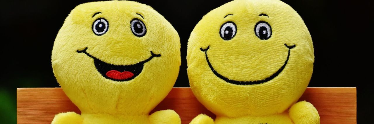 two smiley face stuffed toys sitting on a bench