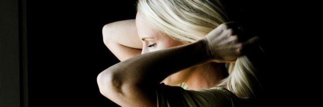 woman in darkness tying hair behind her head in ponytail or bun