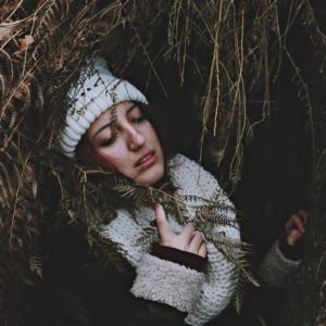 upset woman lying in long grass with hand to chest