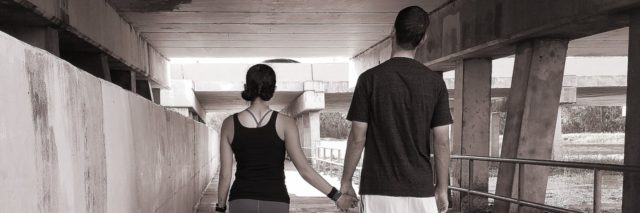 man and woman walking together and holding hands