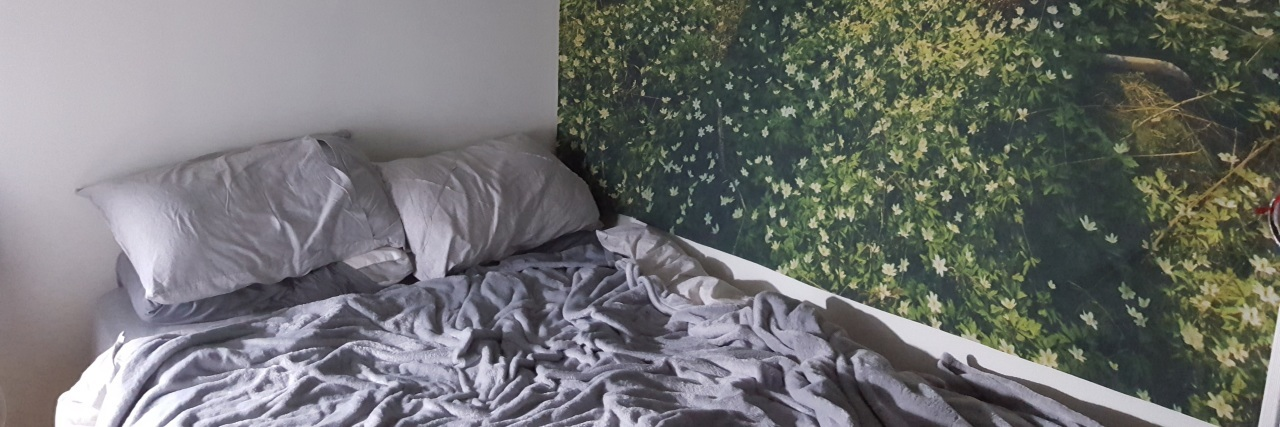 bed with mural hanging on the wall