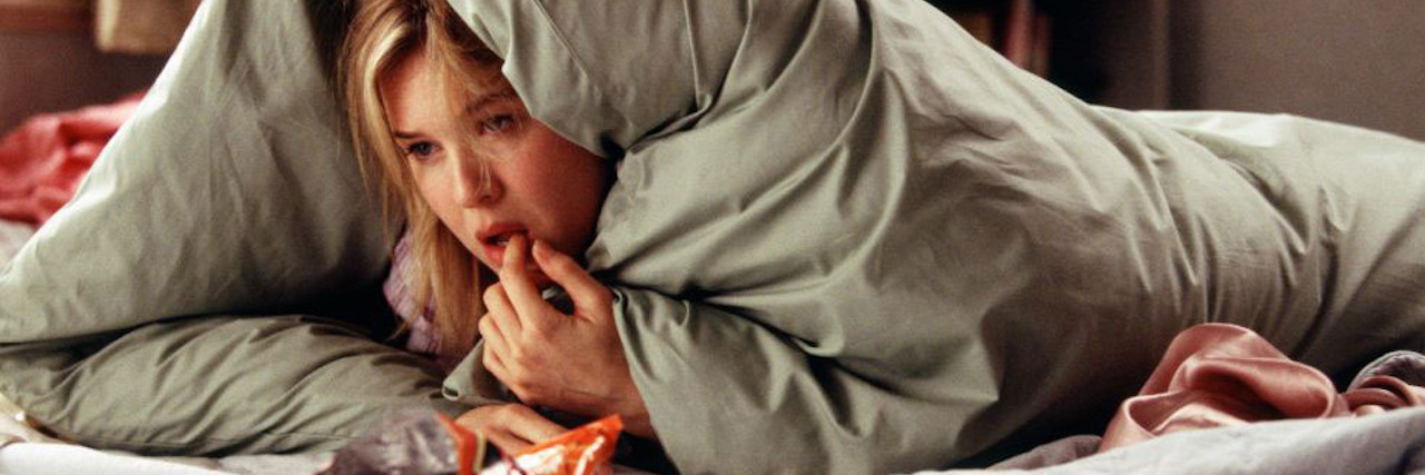 bridget jones curled up in bed eating snacks