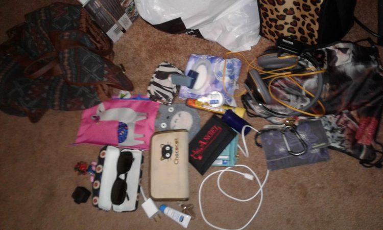 assortment of things on the floor, sunglasses, wallet, small cases