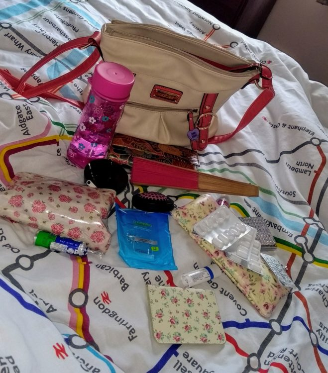 tan purse sitting on bed with medications and small pouches