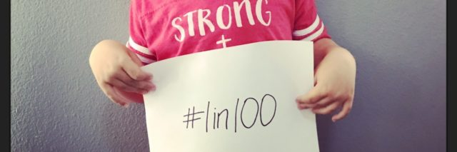 The author's son, holding a sign that says [hashtag] 1 in 100