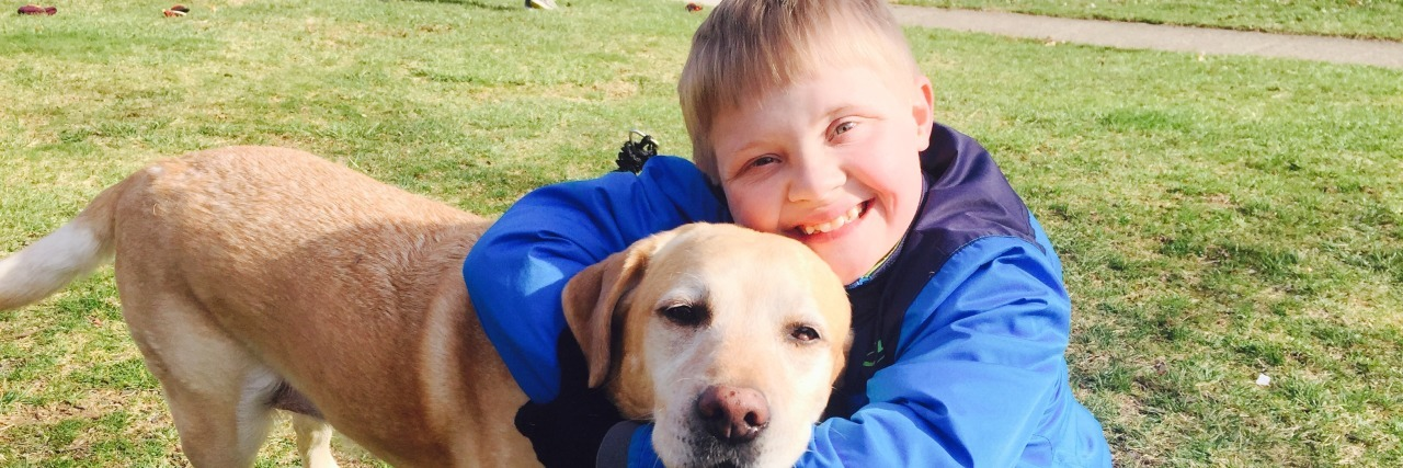 Boy with Down syndrome hugging his brown dog