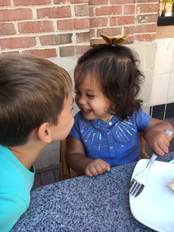 Brother and sister looking at each other and laughing