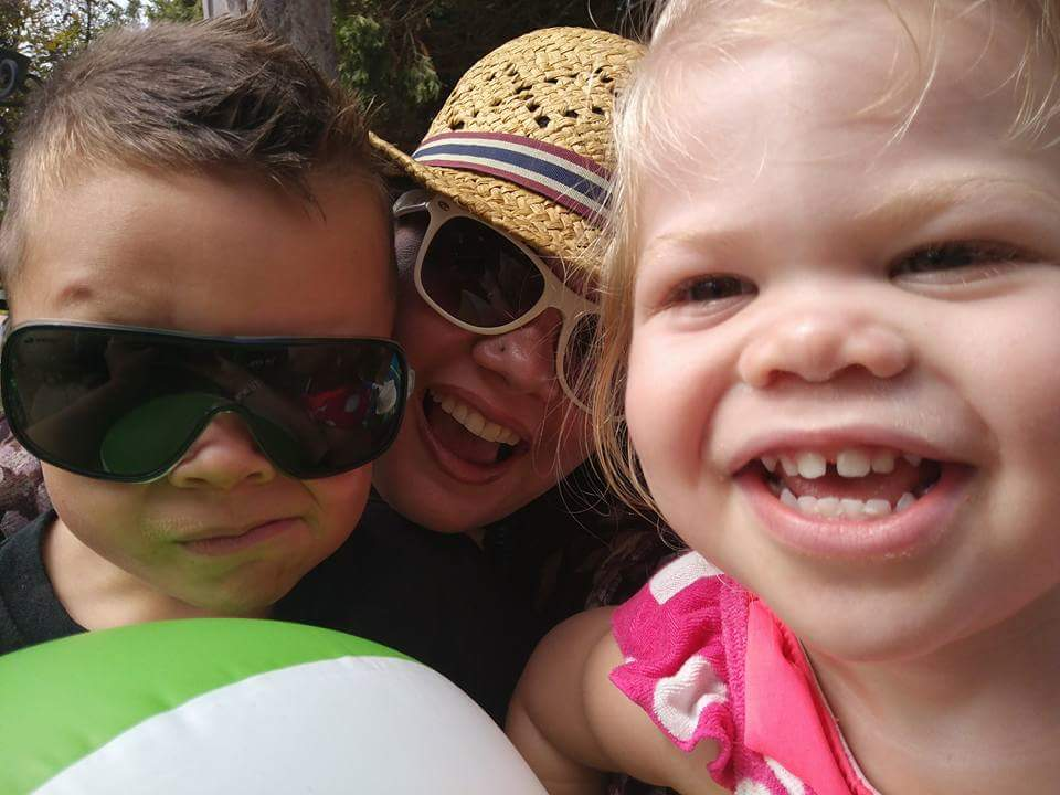 mother smiling with two children wearing sunglasses