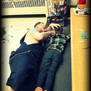 Viral photo of barber Jakob on the floor cutting Wyatt Lafreniere's hair. Wyatt is on the autism spectrum.