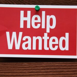 Help Wanted Sign on a wood background.