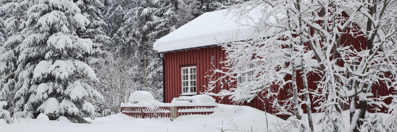 Charming red house with snow on the roof in winter.