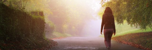 A solitary woman walking on a country road.