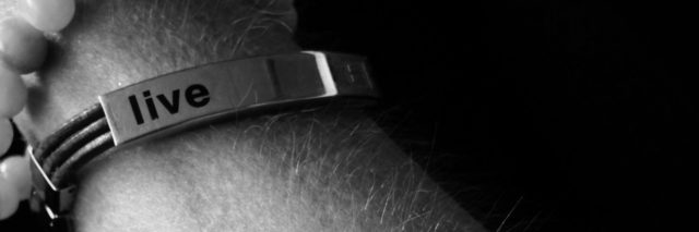 black and white photo of a woman's arm with a bracelet that says 'live' and an IV in her arm