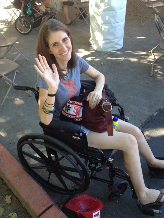michaela oconnor waving in a wheelchair