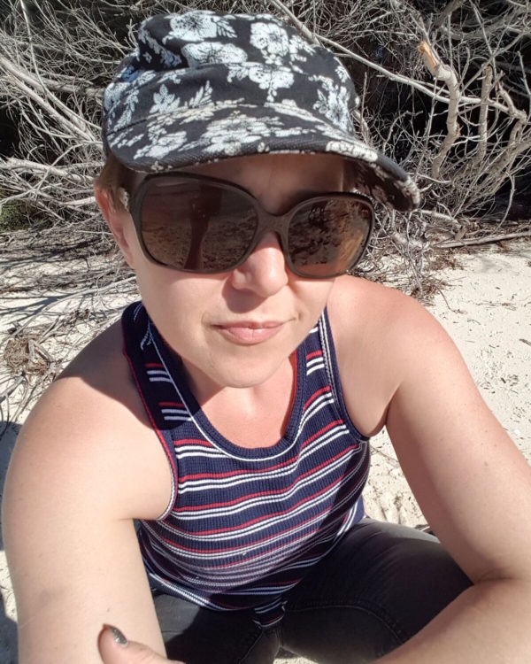woman sitting on the beach in a hat and sunglasses