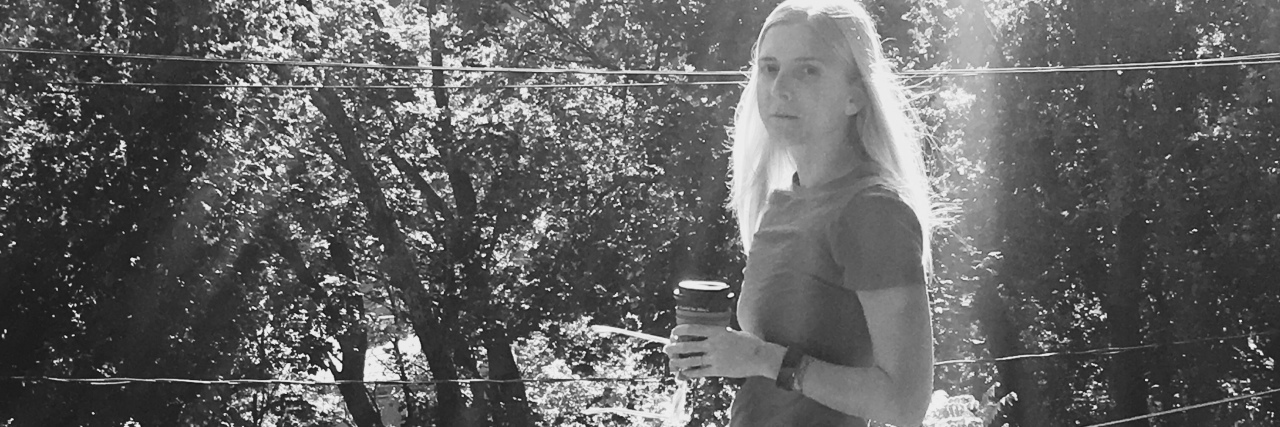 black and white photo of a woman standing outside holding coffee