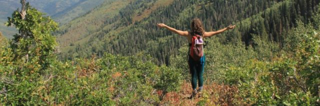 woman standing in mountains with arms outstretched