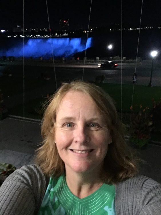author in front of niagara falls