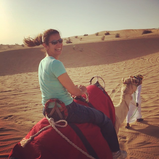 Riding a camel in the desert.