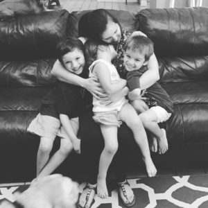 Black and white picture of mother holding her three children