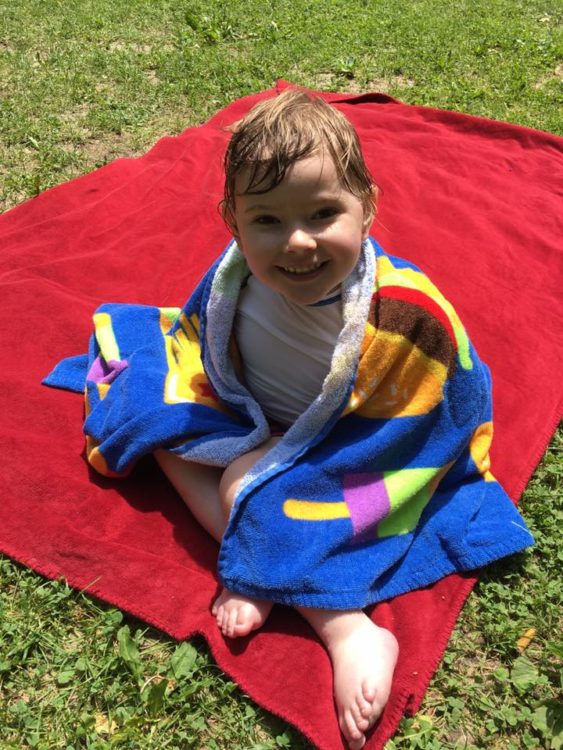 Boy sitting on blanket with towel around him after swimming