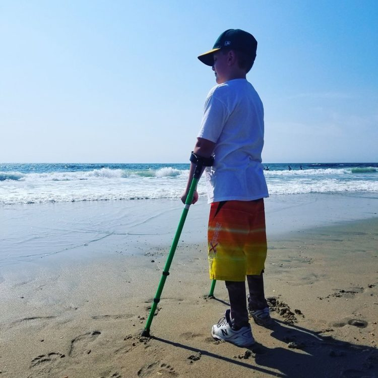 Boy standing by the ocean using crutches
