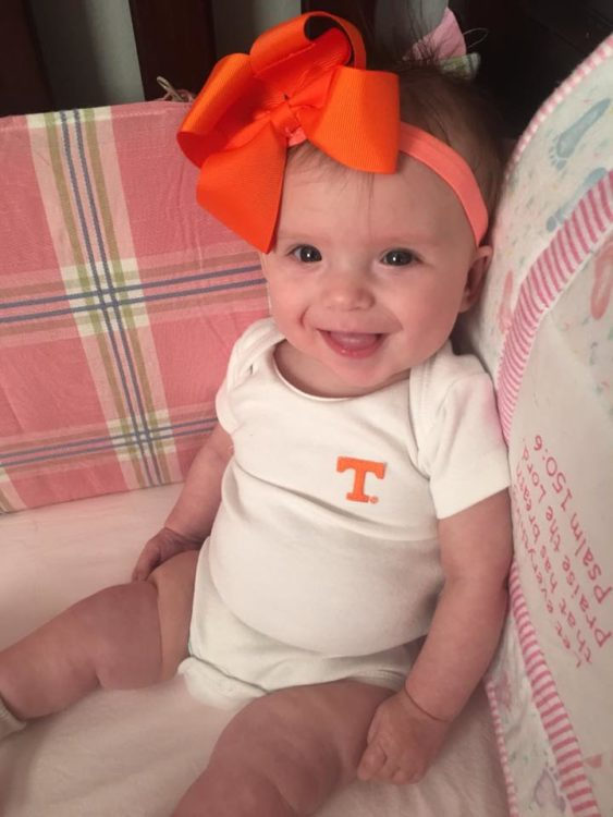 Baby girl with big orange bow sitting on a couch