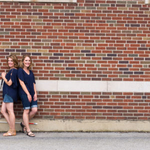 Jenelle with her twin sister, both standing against a brick wall with their matching canes.