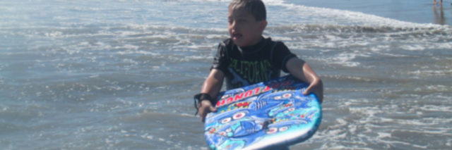 The author's son, holding a boogie board while in the ocean near the shore