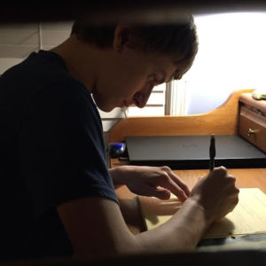 The author's son, working on homework at his desk