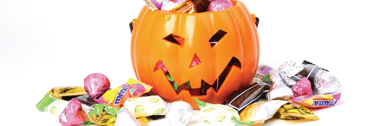 pumpkin halloween bucket with candy overflowing from it