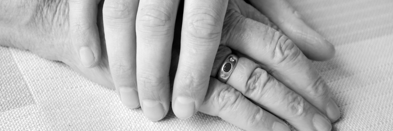 young hand on top of old person's hand in black and white