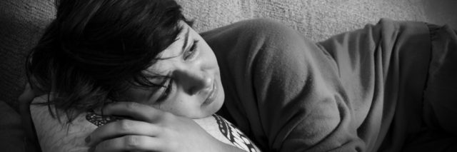 A depressed young woman lying on a couch in black and white