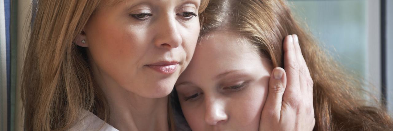 mother comforting sad daughter through struggle