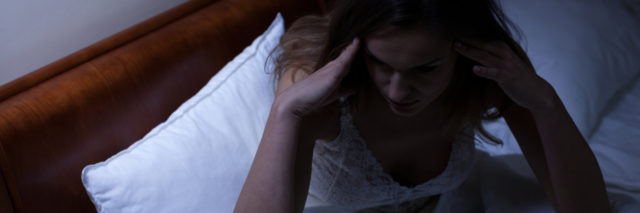 women sitting up in bed unable to sleep