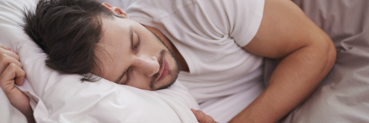 man resting and holding a pillow