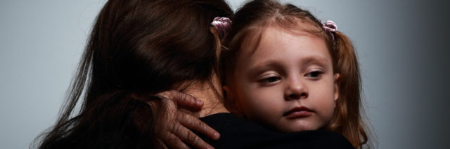 Small sad daughter hugging her mother with love on dark background